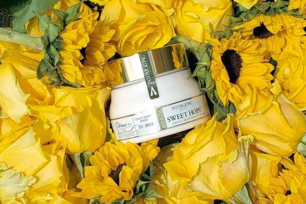 Sweet Hops Body Butter on a bed of sunflowers - keep your skin moisturized with natural ingredients including hops. Learn how hops benefit beauty and wellness.