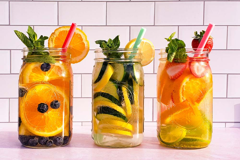3 jars of water infused with various fruits and vegetables. Colorful straws sticking out of the jar.