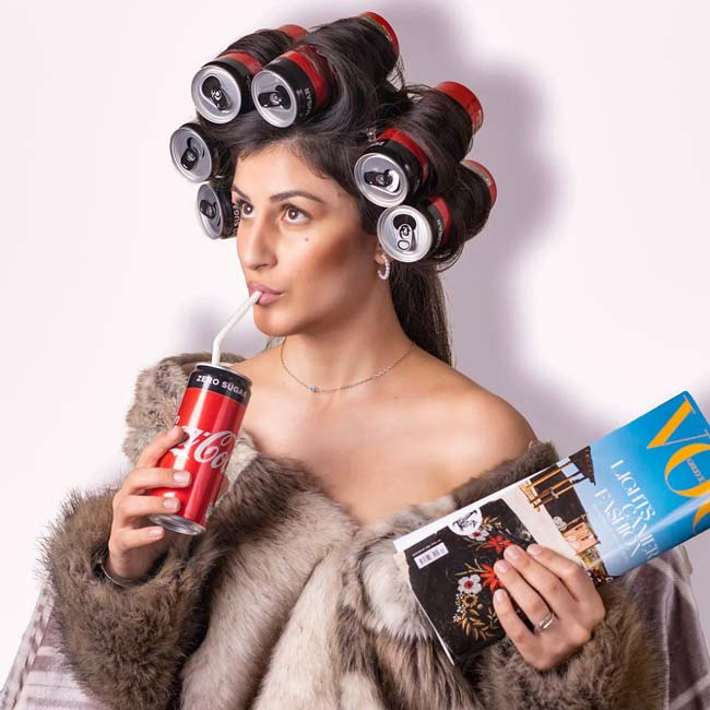 Woman in a faux fur coat with soda cans as hair rollers drinking zero sugar soda through a straw and holding a magazine.