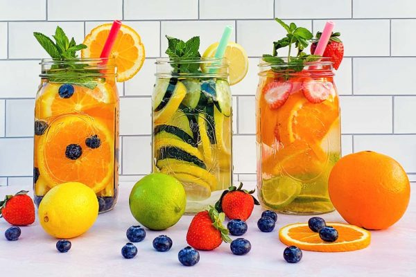 Several jars of fruit and vegetable infused water with fruits in them on a table with fruits scattered around.