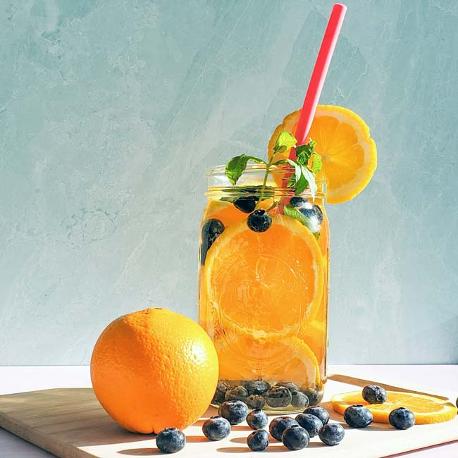 Orange infused water, mixed with blueberries and mint, sitting on a cuitting board, pink straw coming out of the drink.
